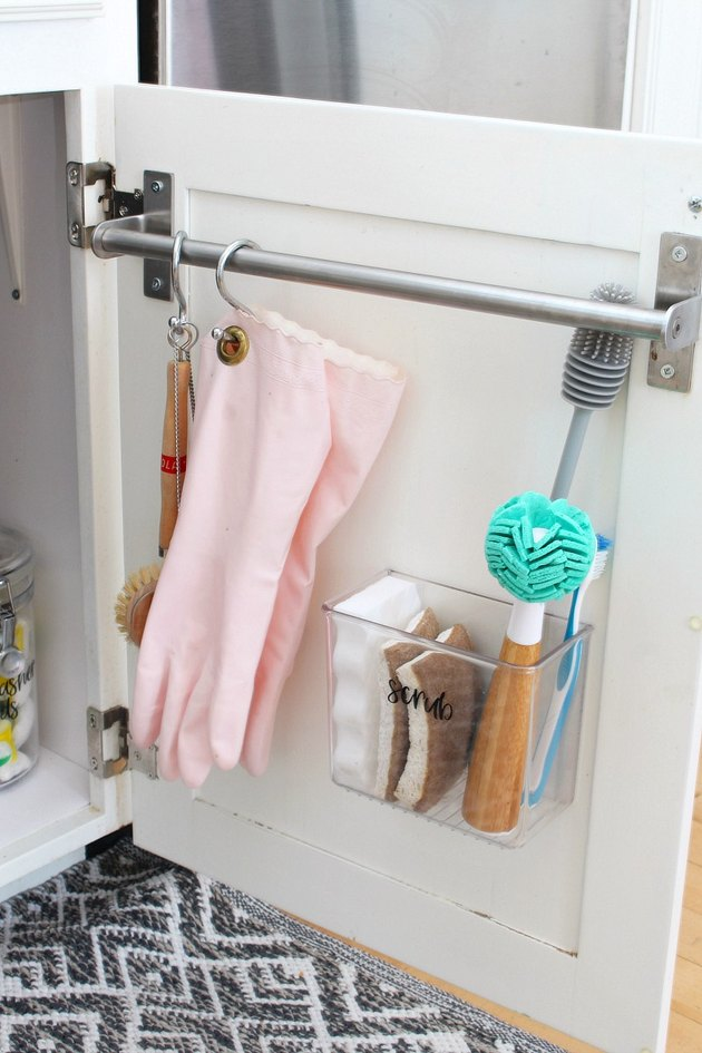 under sink storage with towel bar with pink gloves and scrub brushes hanging on white cabinet door