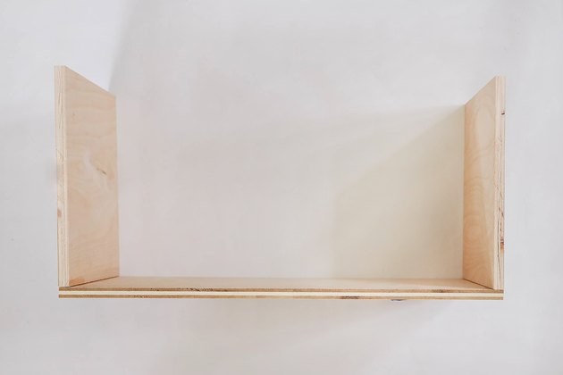 Three boards assembled into bottom floor of dollhouse