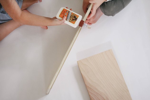 Two kids gluing wood boards together
