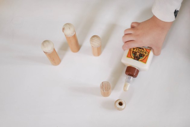 Gluing wood beads onto wood dowels to make dolls