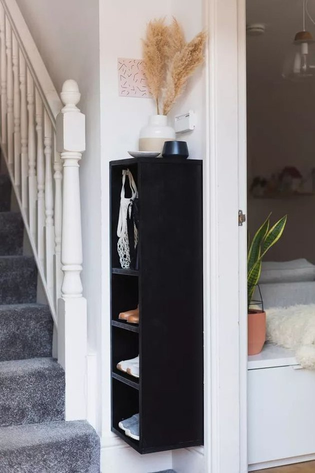 slim wall-mounted shelving unit used for entryway shoe storage