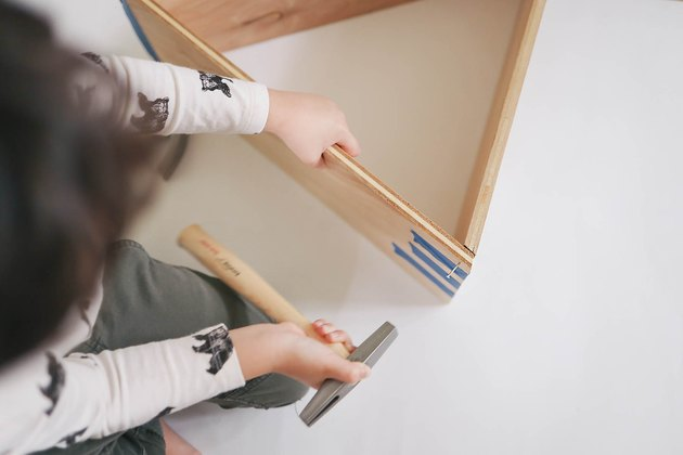 Little boy hammering nail into dollhouse with tack hammer
