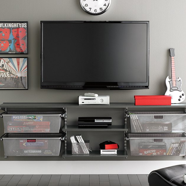 gray walls with media center and TV hanging and board game storage