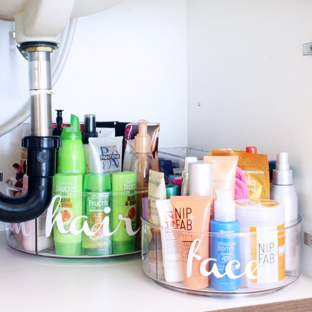 under sink storage with clear labeled containers with beauty products under bathroom sink