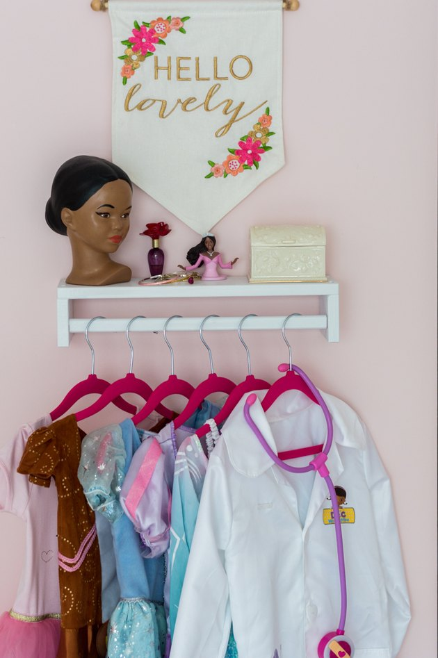 Kids' room organization with pink walls and dress-up area