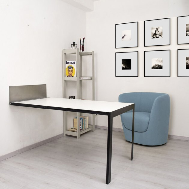 table near shelf and blue chair, with framed prints on the wall