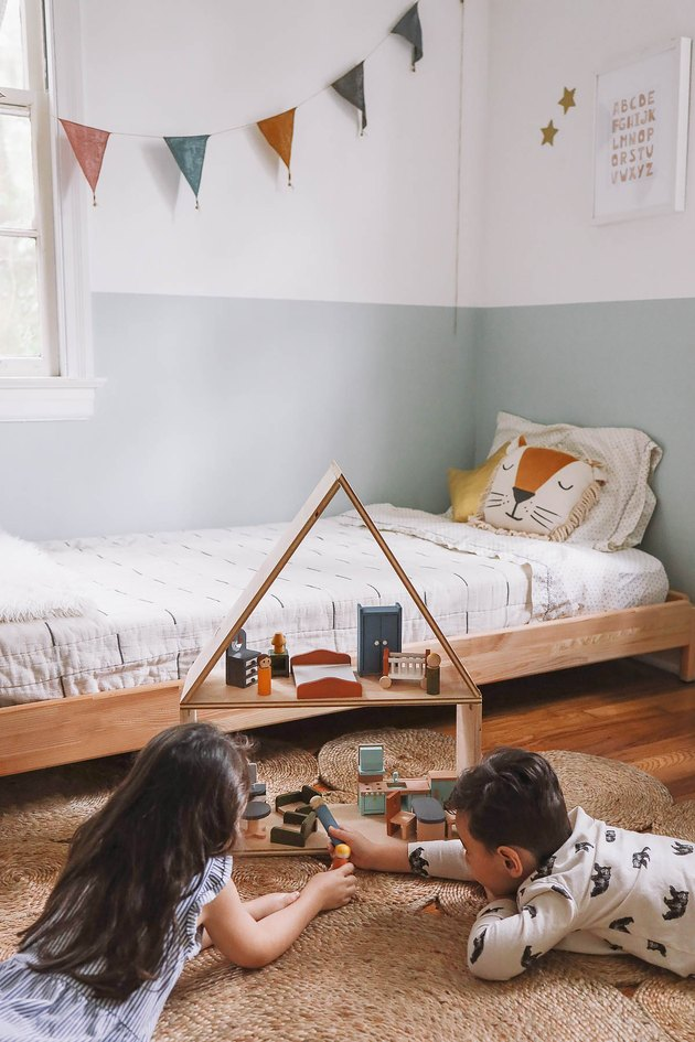 Little girl and boy laying on floor playing with wooden dollhouse in kids' room