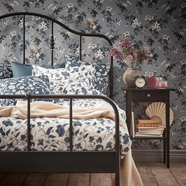 bedroom with floral wallpaper and floral sheets and black night stand