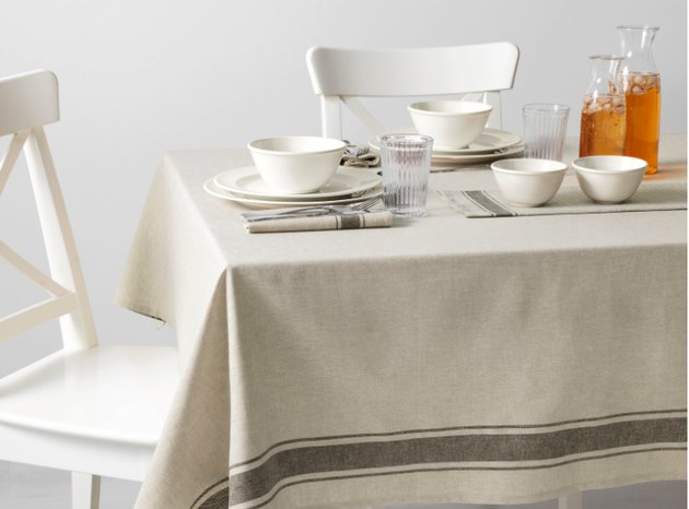 dining scene with white chairs and off-white tablecloth