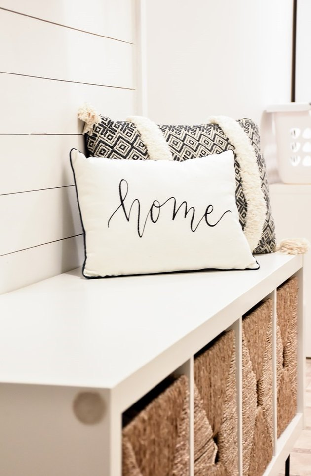 DIY storage bench with white top and baskets with throw pillows