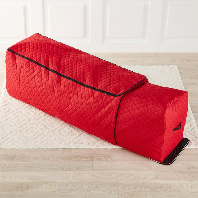 Red quilted Christmas tree storage bag with expandable option on white rug