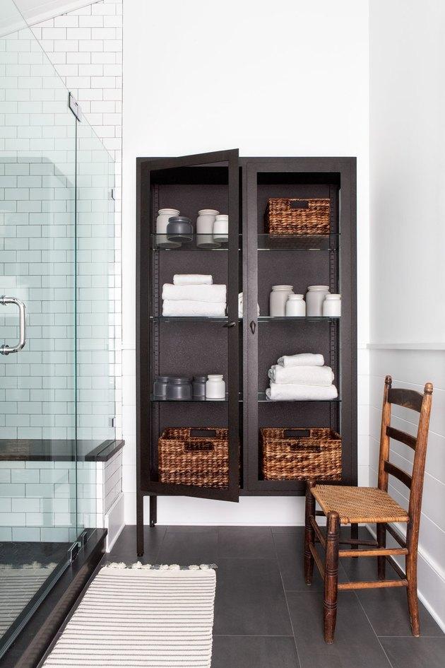 black freestanding cabinet next to shower for bathroom shelving