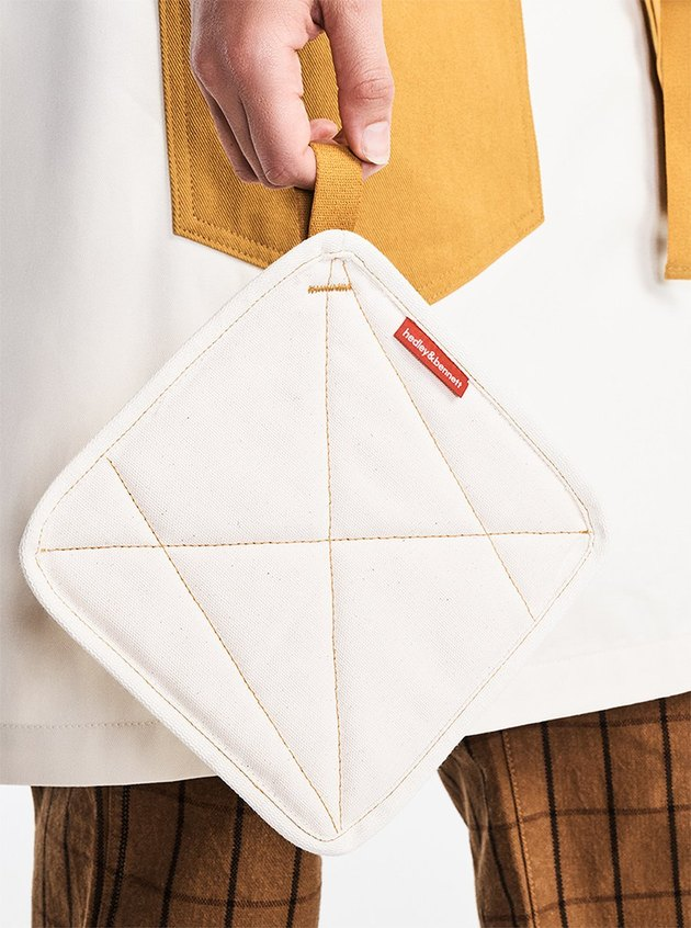 person holding potholder in hand with contrast-stitch pattern