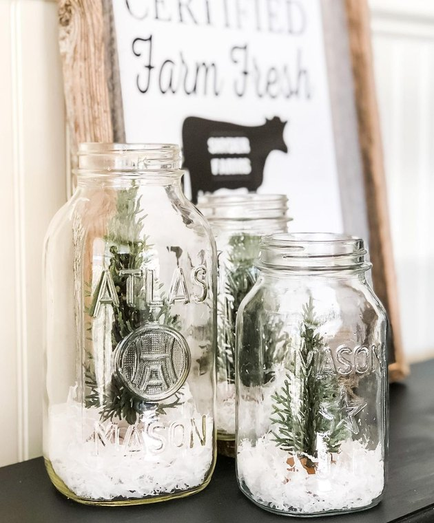 two Mason jars with faux snow and trees