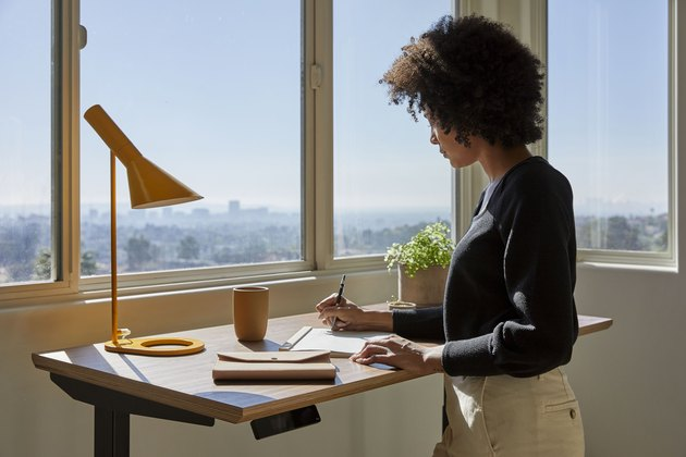 person at standing desk with lamp near window