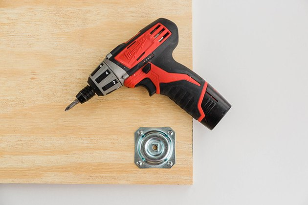Fixez les plaques de pied de table aux coins de la planche de contreplaqué.