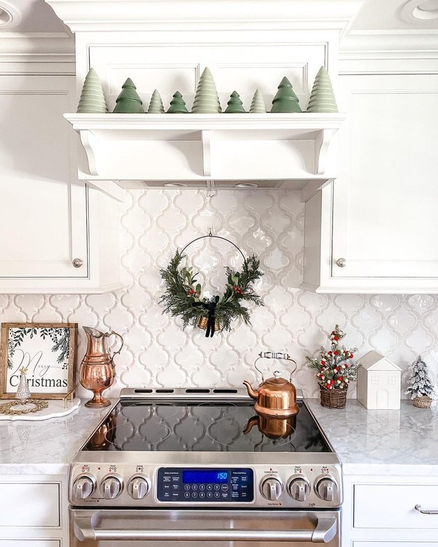 kitchen with trees on shelf and wreath on backsplash
