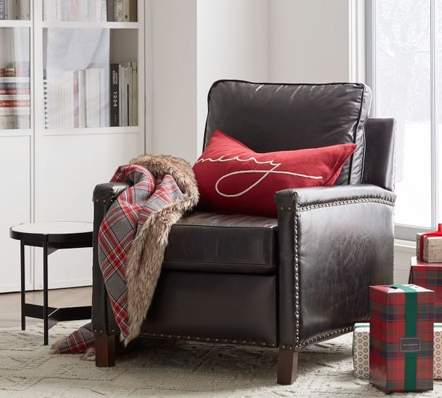 chair with red pillow and plaid throw blanket