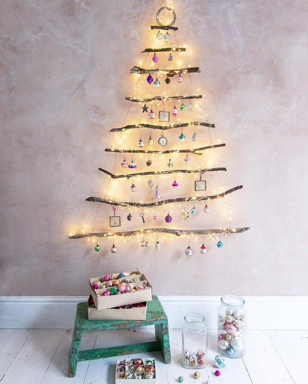 tree branches and lights on wall with stool and books nearby