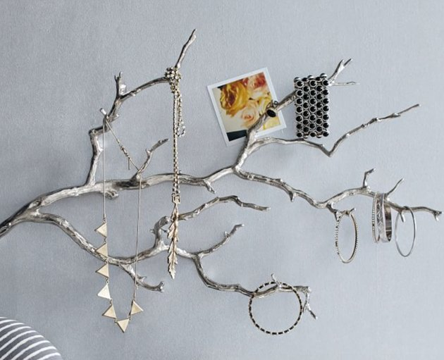 Earring Storage with Silver finished branch on wall with jewelry hanging.