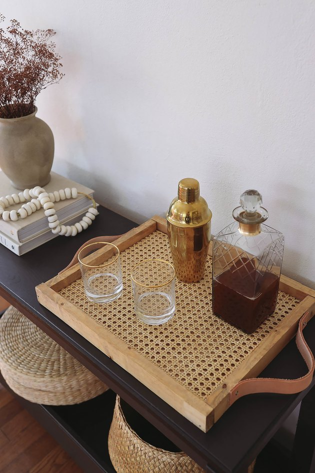 DIY cane webbing tray on table with cocktail shaker, decanter and glasses