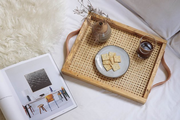 Cane and leather tray on bed