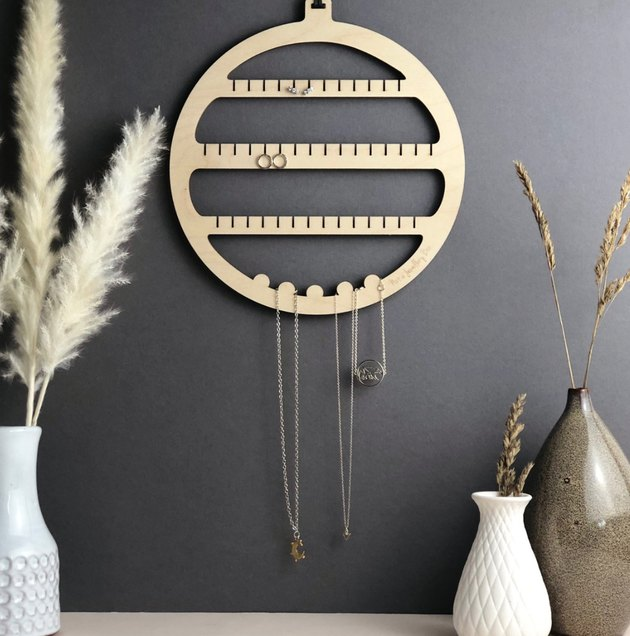 Earring Storage with Wood jewelry organizer, ceramic vases with flowers, dark gray wall.