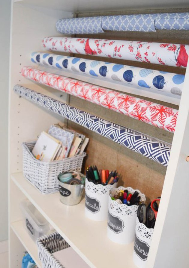 wrapping paper storage idea with stacked reams and cups for pens