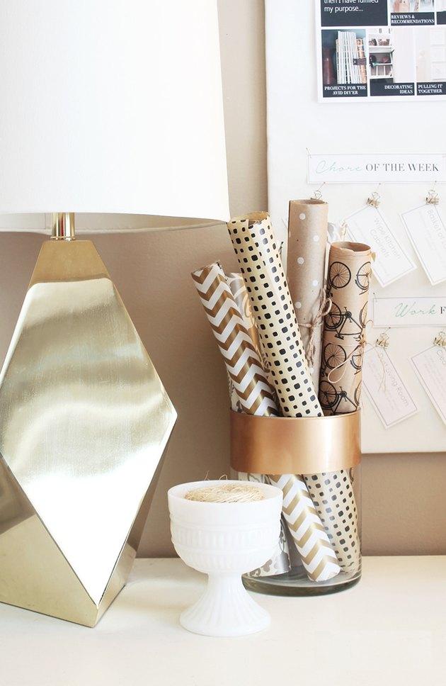 wrapping paper storage idea on desktop in glass jar