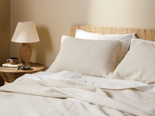 cream bedding with natural woven headboard and bedside table