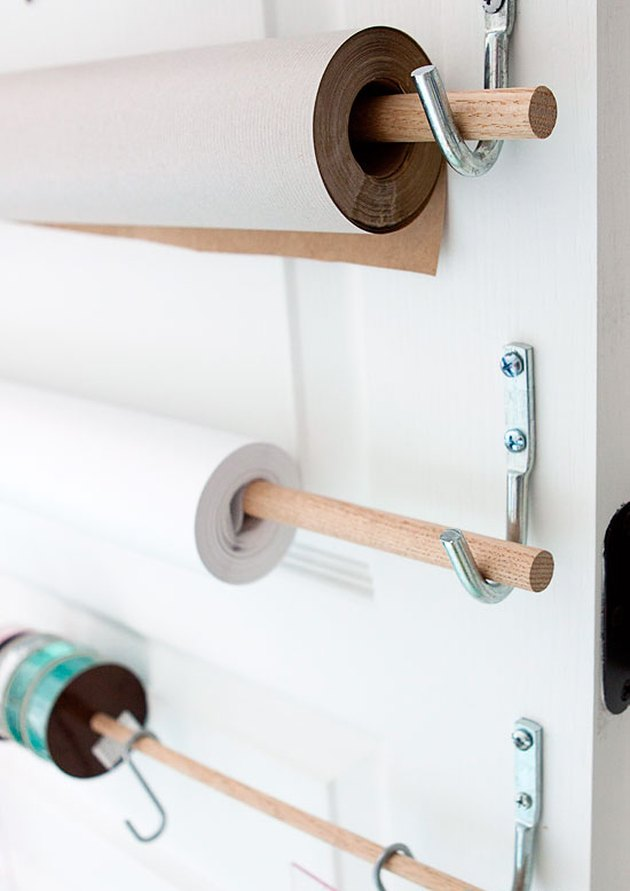 wrapping paper storage idea on back of door with wooden dowels