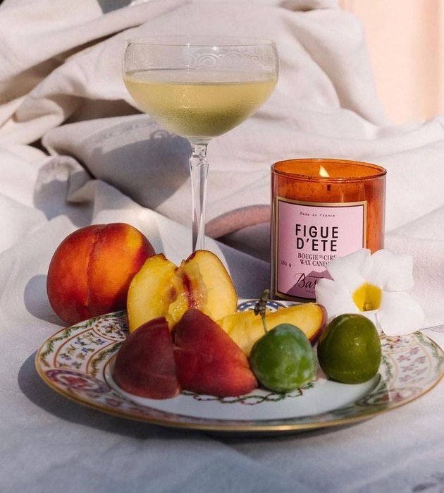 Bastide's Figue d'Ete Candle  next to plate of fruit and glass of wine