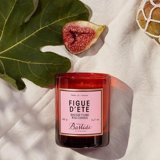 Bastide's Figue d'Ete Candle next to fig and green leaf