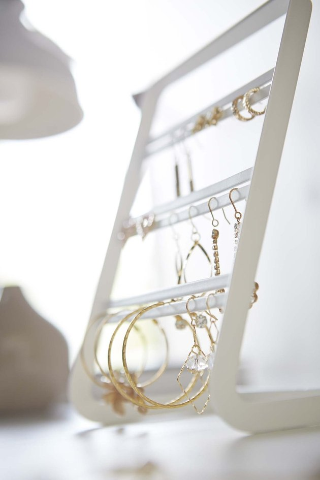 Earring Storage with White jewelry organizer with gold earrings.
