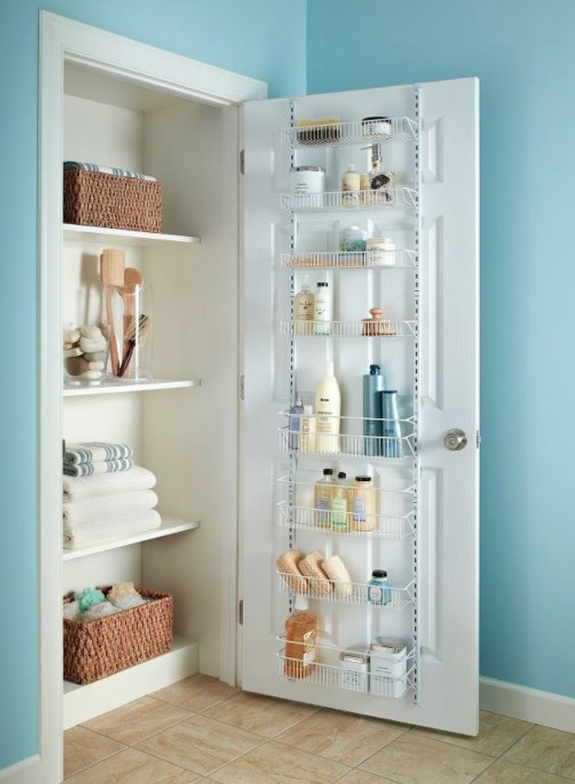 Closet organizer with linens, door rack with cleaning supplies.