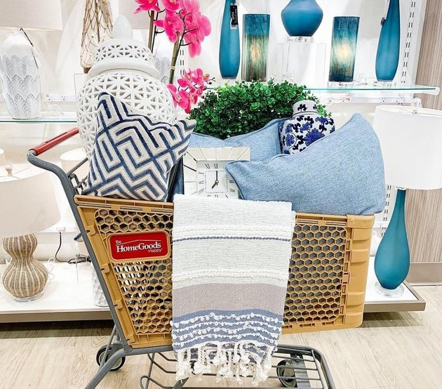 homegoods shopping. cart filled with pillows in front of blue lamps
