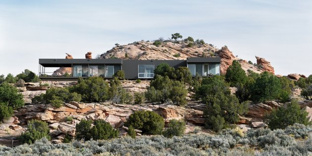 black contemporary ranch home set amongst red rocks
