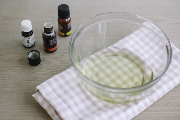 Essential oils next to bowl of melted soy wax