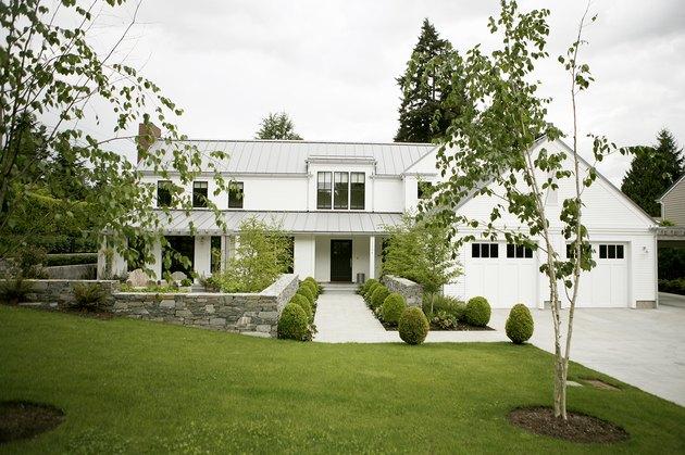 modern white farmhouse with boxwood shrubs