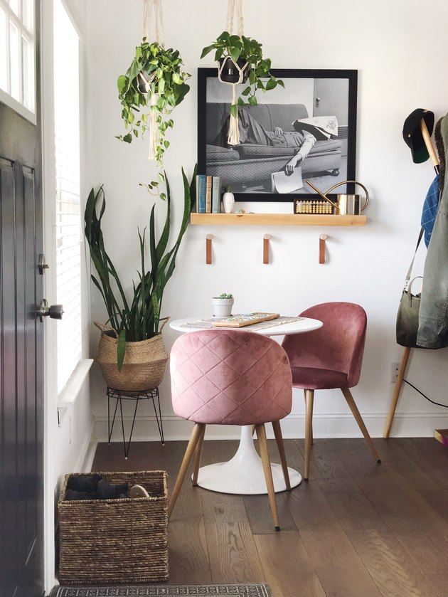Woven entryway shoe storage with basket in entryway next to table and pink chairs