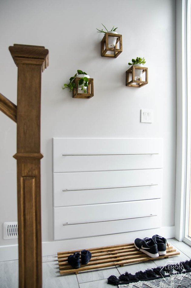 entryway shoe storage with minimalist wood mat in white entryway with hanging plants on wall