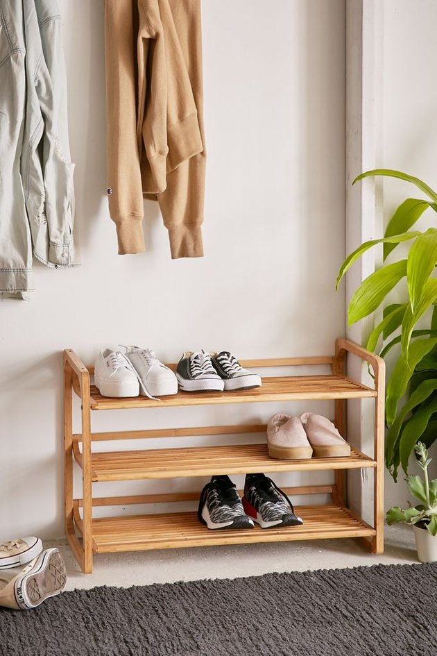 Bamboo rack for entryway shoe storage with a few pairs of shoes in entryway