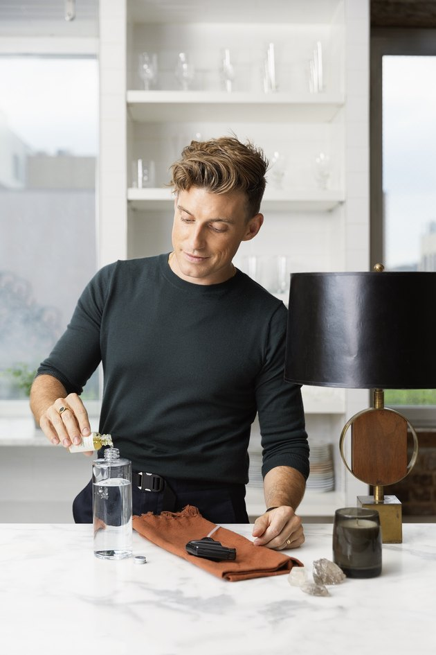 jeremiah brent pouring something into bottle in kitchen area with shelves in the background