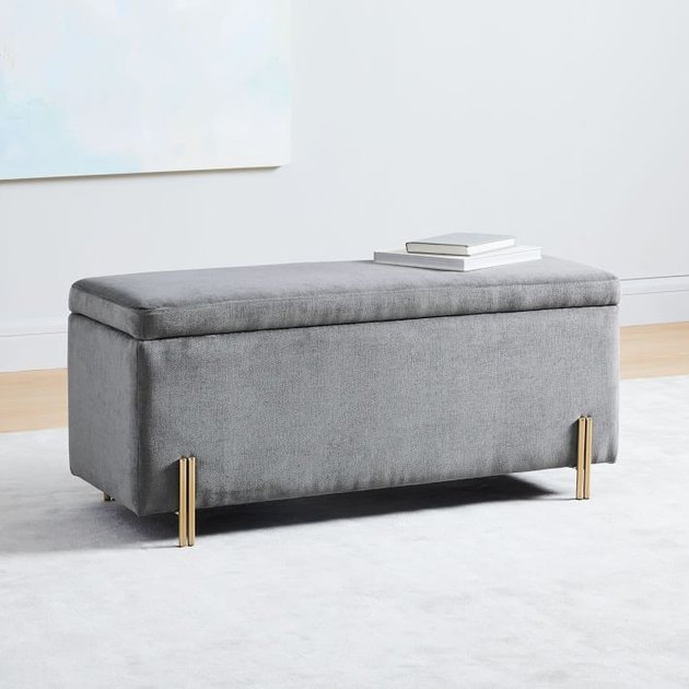 gray velvet cushioned bedroom storage bench with books on top