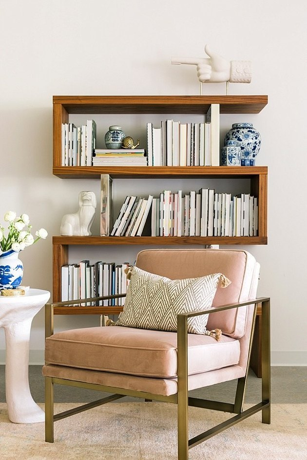 How To Organize a Bookshelf in room with rose upholstered and metal lounge chair, art, flowers, books.