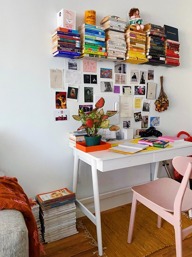 How To Organize a Bookshelf in Home office with white desk, pink chair, books stacked on shelf, art, plant.