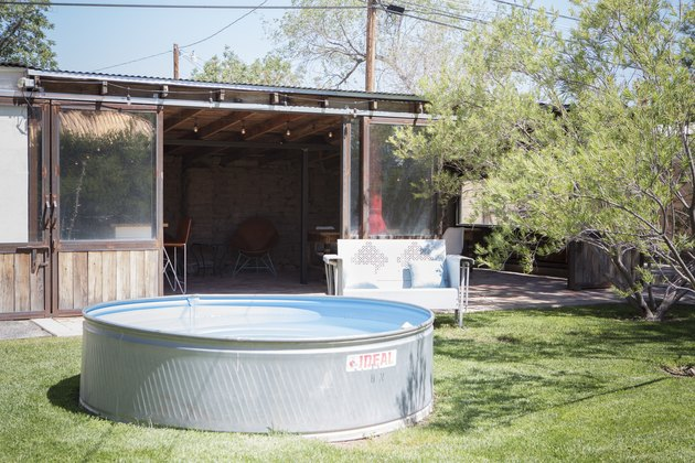 A stock tank pool sitting in front of a garden shed
