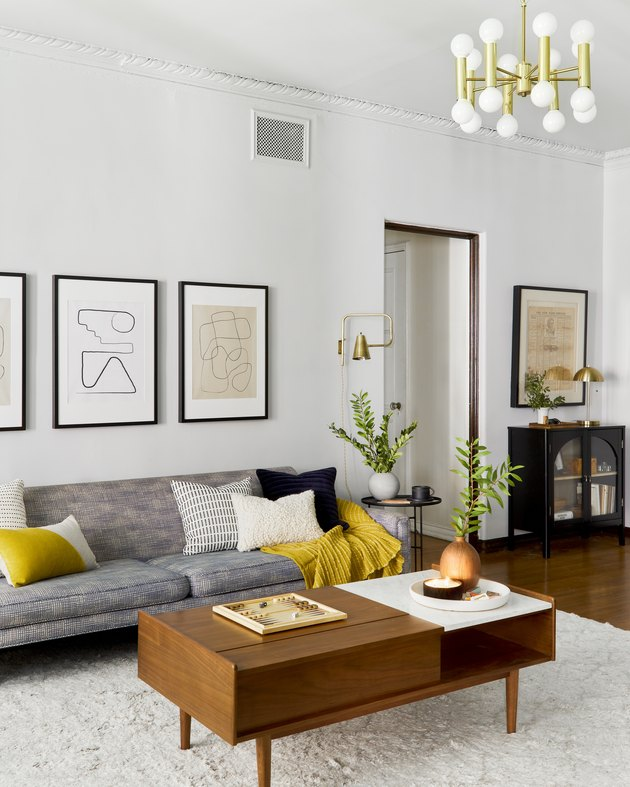 living room space with gray couch and framed artwork on the wall