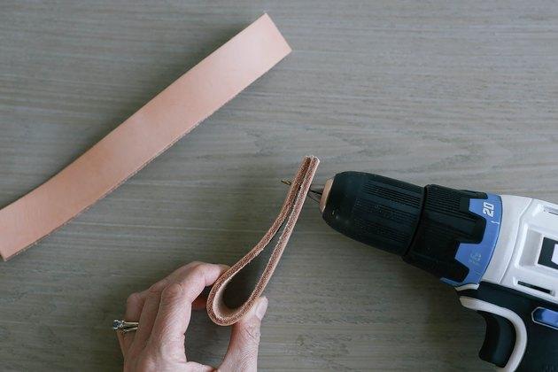 Bande de cuir pliante en deux et percer un trou pilote à travers les extrémités