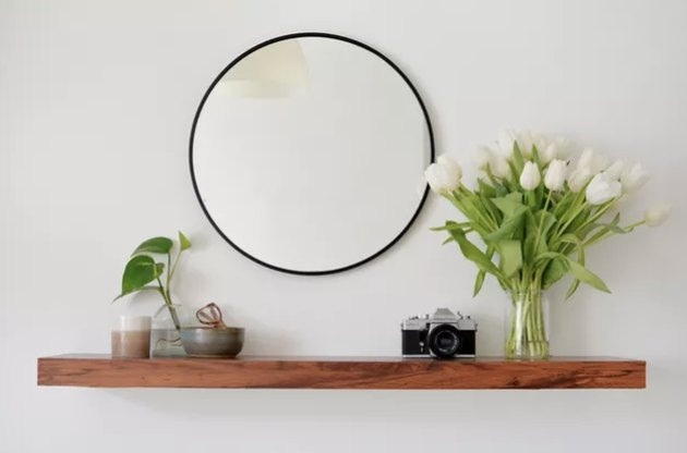 IKEA Lack shelf with walnut cover, mirror, and flowers